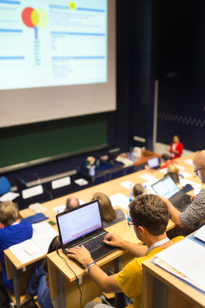 computer program: Workshop at university. Rear view of students sitting and listening in lecture hall doing practical tasks on their laptops.