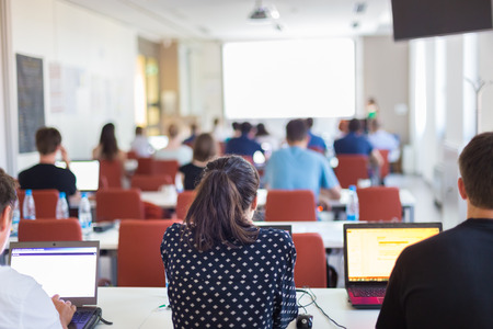 curso de capacitacion: Altavoz dar una charla en la reunión de negocios. Vista trasera de la audiencia en la sala de conferencias. Negocios y Emprendimiento. Copie el espacio en la tarjeta blanca.