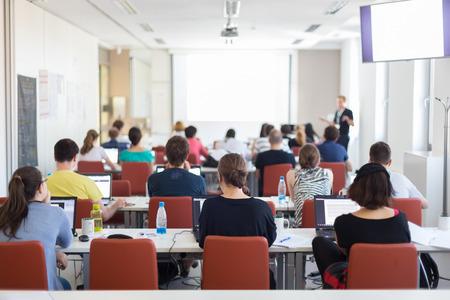 estudiantes universitarios: Taller en la universidad. Vista trasera de los estudiantes sentados y escuchando en sala de conferencias haciendo tareas prácticas en sus computadoras portátiles.