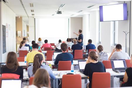 programing: Taller en la universidad. Vista trasera de los estudiantes sentados y escuchando en sala de conferencias haciendo tareas pr�cticas en sus computadoras port�tiles. Copie el espacio en la pantalla blanca.