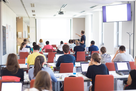 practical: Workshop at university. Rear view of students sitting and listening in lecture hall doing practical tasks on their laptops. Copy space on white screen. Stock Photo