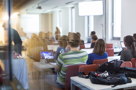 training workshop: Workshop at university. Rear, trough the window, view of students sitting and listening in lecture hall doing practical tasks on their laptops. Stock Photo