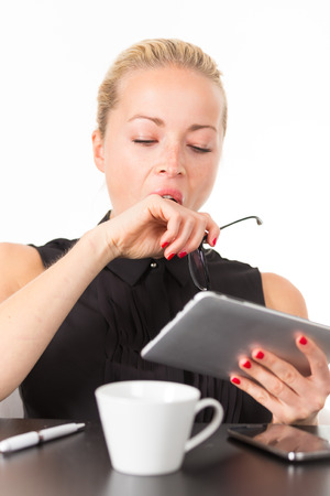 woman work: Business woman yawning while working on her tablet PC.