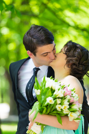 romantic couple: Valentines Day. Love is in the air. Portrait of a loving couple kissing in the park. Lady holding a big bouquet of tulips. Stock Photo