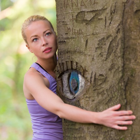 Relaxed young lady embracing a tree receiving life energy from the nature. Eye carved in tree trunk.