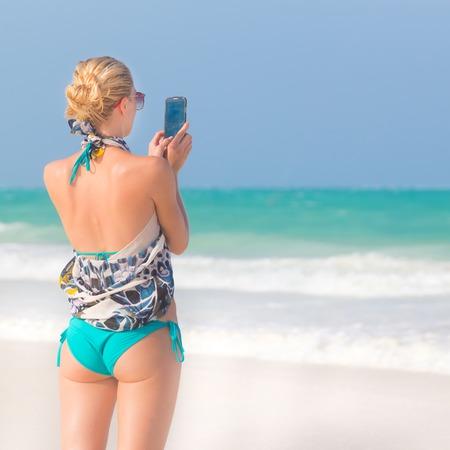 vacaciones en la playa: Mujer caucásica rubia toma la foto de azul playa tropical. Modelo caucásica hermosa vistiendo traje de baño turquesa y bufanda de colores en las vacaciones en la imagen perfecta playa de Paje, Zanzibar, Tanzania.