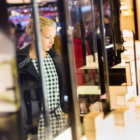 美しいブロンドの女性の美しさのストアでのショーケースの前に立って、新しい香水のコレクションを眺めします。