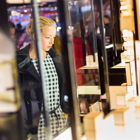 아름 다운 금발 여자, 아름다움 저장소 쇼케이스 앞에 서 새로운 향수 컬렉션을 감상.