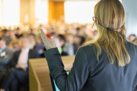 female teacher: Female speaker at Business Conference and Presentation. Audience at the conference hall. Business and Entrepreneurship. Business woman. Stock Photo