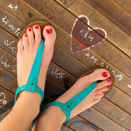 woman sandals: Graphical image of beautiful healthy female feet with red nailpolish applied on the nails wearing turquoise summer leather sandals standing by heart shaped graffiti drawn on a wooden surface. Stock Photo