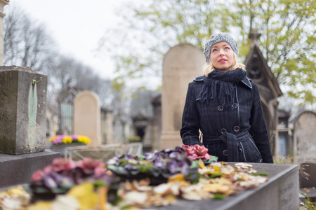 grave: Solitary woman mourning by gravestone, remembering dead relatives in on Pere Lachaise cemetery in Paris, France.