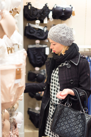 woman shop: Woman shopping lingerie . Shopper looking and choosing clothing indoors in store. Beautiful blonde caucasian female model wearing winter coat and fashionable knitted cap.
