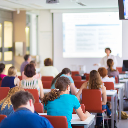 Speaker giving presentation in lecture hall at university. Participants listening to lecture and making notes. Stock Photo
