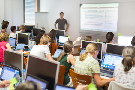 PC: Workshop at university. Rear view of students sitting and listening in lecture hall doing practical exercises on their laptop computers.  Tutor explaining tasks on white board.