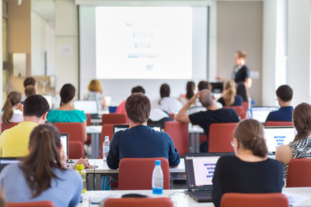 Workshop at university. Rear view of students sitting and listening in lecture hall doing practical tasks on their laptops. Copy space on white screen. Foto de archivo