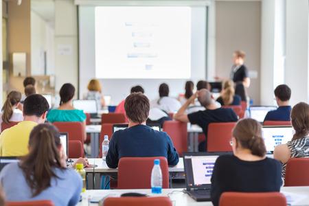 estudiantes universitarios: Taller en la universidad. Vista trasera de los estudiantes sentados y escuchando en sala de conferencias haciendo tareas pr�cticas en sus computadoras port�tiles. Copie el espacio en la pantalla blanca.