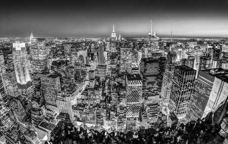 office building exterior: New York City. Manhattan downtown skyline with illuminated Empire State Building and skyscrapers at dusk seen from observation deck. Panoramic view. Black and white photo. Stock Photo