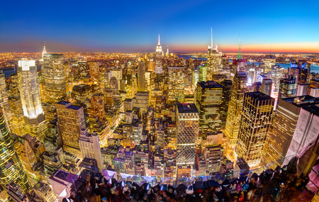 empire state building: New York City. Manhattan downtown skyline with illuminated Empire State Building and skyscrapers at dusk seen from observation deck. Panoramic view.