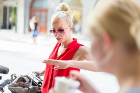 socializando: Es bueno verte. Ha pasado un tiempo. Dos felices jóvenes amigas goza de una conversación en una calle de la ciudad acera al azar después del encuentro de trabajo. Agradable socialización tiempo libre.