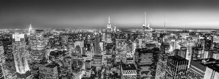 New York City. Manhattan downtown skyline with illuminated Empire State Building and skyscrapers at dusk seen from observation deck. Panoramic view. Black and white photo. Stock Photo