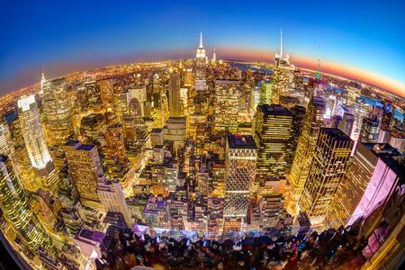 comercio: Nueva York. Horizonte de la ciudad de Manhattan con sistema de iluminación del Empire State Building y rascacielos al atardecer visto desde la cubierta de observación. Vista panorámica de ojo de pescado.