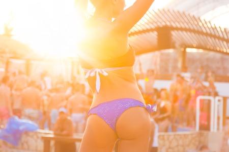 Sexy hete meisje dat Braziliaanse bikini dansen op een strand feest evenement in zonsondergang. Menigte dansen en partyingat zwembad in de achtergrond. Zomer festival voor elektronische muziek. Hete zomer party vibe. Stockfoto