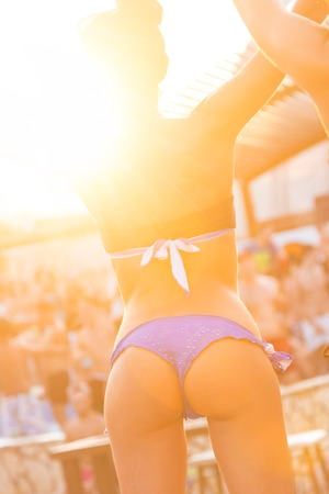 go go dancer: Sexy hot girl wearing brazilian bikini dancing on a beach party event in sunset. Crowd dancing and partyingat poolside in background. Summer electronic music festival. Hot summer party vibe.
