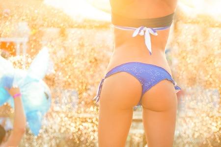 cuerpo femenino: Chica caliente atractiva que desgasta el baile bikini brasileño en un evento de fiesta en la playa en la puesta del sol. Multitud de fiesta en lluvia de gotas de oro en el fondo. Summer festival de música electrónica. Hot ambiente de fiesta de verano.