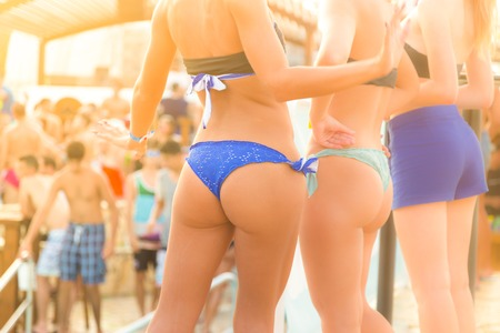 hintern: Sexy heiße Mädchen, das brasilianische Bikinitanzen am Strand Party-Event im Sonnenuntergang. Menschenmenge feiern in der Dusche der goldenen Tropfen im Hintergrund. Sommer-Festival für elektronische Musik. Heiße Sommerpartystimmung. Lizenzfreie Bilder