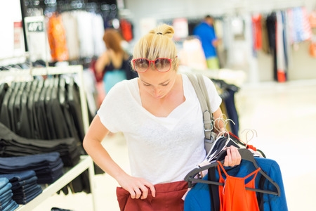 coat hanger: Woman shopping clothes. Shopper looking at clothing indoors in store. Beautiful blonde caucasian female model wearing casual clothes and fashionable sunglasses. Focus on model, shallow depth of field.