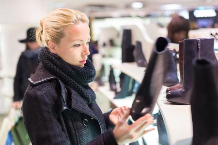 comprando zapatos: Zapatos de compras Mujer. Shopper mirando botas altas ancle en estante de exhibición en la tienda de zapatos. Hermosa modelo femenino caucásico.