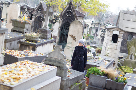 remembering: Solitary woman mourning by gravestone, remembering dead relatives in on Pere Lachaise cemetery in Paris, France.