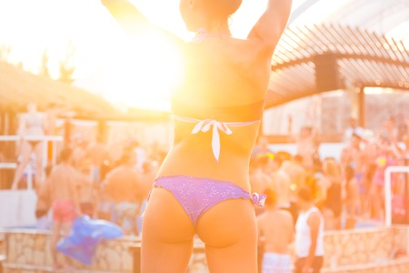 sexy young girl: Sexy hot girl wearing brazilian bikini dancing on a beach party event in sunset. Crowd dancing and partying at poolside in background. Summer electronic music festival. Hot summer party vibe.