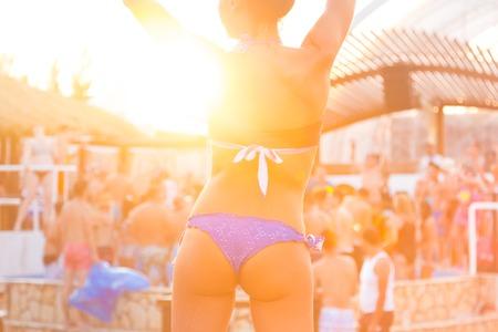 donna che balla: Sexy ragazza calda indossando bikini brasiliana che balla su un evento di festa in spiaggia nel tramonto. Folla danza e festa a bordo piscina in background. Estate festival di musica elettronica. Estate calda atmosfera di festa. Archivio Fotografico