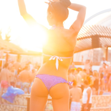 party background: Sexy hot girl wearing brazilian bikini dancing on a beach party event in sunset. Crowd dancing and partying at poolside in background. Summer electronic music festival. Hot summer party vibe.