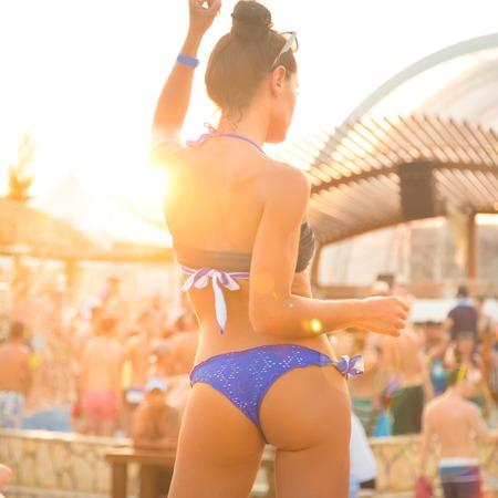 hintern: Sexy heiße Mädchen, das brasilianische Bikinitanzen am Strand Party-Event in Sonnenuntergang. Crowd Tanzen und Feiern am Pool im Hintergrund. Sommer-Festival für elektronische Musik. Heiße Sommerpartystimmung.