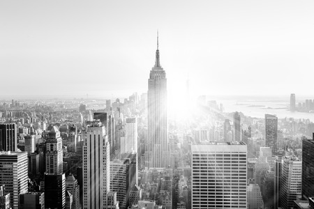 cities: New York City. Manhattan downtown skyline with illuminated Empire State Building and skyscrapers at sunset. Vertical composition. Sunbeams and lens flare. Black and white image. Stock Photo