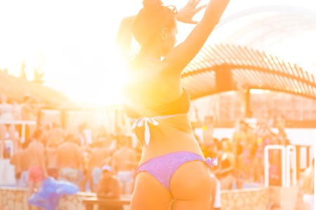 ibiza: Sexy hot girl wearing brazilian bikini dancing on a beach party event in sunset. Crowd dancing and partying at poolside in background. Summer electronic music festival. Hot summer party vibe.