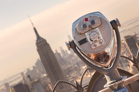 New York City, USA. Vintage tourist binoculars at Top of the Rock observation deck in front of Manhattan downtown skyline with Empire State Building and skyscrapers at sunset. Фото со стока