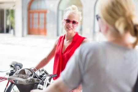 after to work: Es bueno verte. Ha pasado un tiempo. Dos felices j�venes amigas goza de una conversaci�n en una calle de la ciudad acera al azar despu�s del encuentro de trabajo. Agradable socializaci�n tiempo libre.