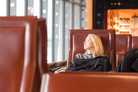 frio: Mujer que viajaba en frío y cansado cubierta con chaqueta de espera para la salida, descansando en el banco de puertas con todo su equipaje a su lado. Tireing viajes de negocios. Foto de archivo