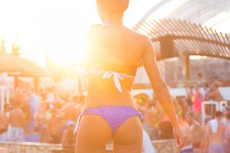 Sexy heiße Mädchen, das brasilianische Bikinitanzen am Strand Party-Event in Sonnenuntergang. Crowd Tanzen und Feiern am Pool im Hintergrund. Sommer-Festival für elektronische Musik. Heiße Sommerpartystimmung.