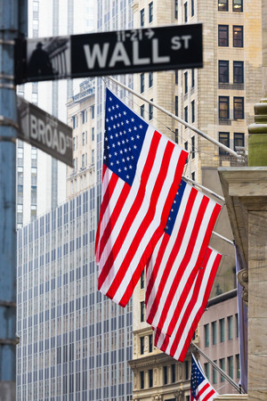 travel industry: Wall street sign in New York with American flags and New York Stock Exchange background. Stock Photo
