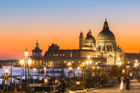 romantico: Romántica ciudad italiana de Venecia en la puesta del sol. Embarcaciones tradicionales venecianas de madera, gondolero y de la iglesia católica romana Basílica de Santa Maria della Salute.