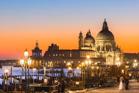 Romantic Italian city of Venice in sunset. Traditional Venetian wooden boats, gondolier and Roman Catholic church Basilica di Santa Maria della Salute.