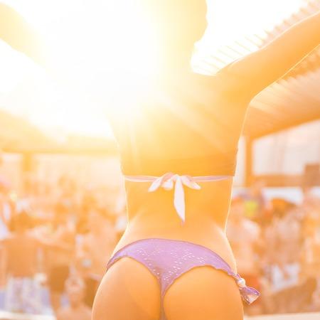 ragazze che ballano: Sexy ragazza calda indossando bikini brasiliana che balla su un evento di festa in spiaggia nel tramonto. Folla danza e festa a bordo piscina in background. Estate festival di musica elettronica. Estate calda atmosfera di festa. Archivio Fotografico