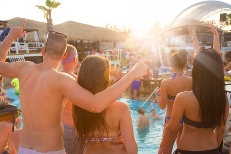 bikini pool: Sexy hot frinds dancing on a beach party event in sunset. Crowd dancing and partying at poolside in background. Summer electronic music festival. Hot summer party vibe. Stock Photo