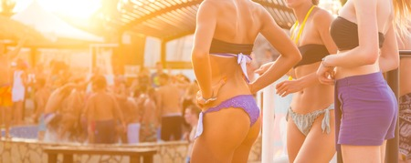 Sexy hot girls wearing brazilian bikini dancing on a beach party event in sunset. Crowd dancing and partying at poolside in background. Summer electronic music festival. Hot summer party vibe.