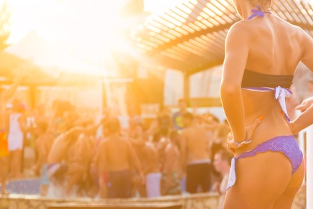 Sexy hete meisje dat Braziliaanse bikini dansen op een strand feest evenement in zonsondergang. Menigte dansen en feesten bij het zwembad in de achtergrond. Zomer festival voor elektronische muziek. Hete zomer party vibe.