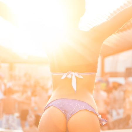 vibe: Sexy hot girl wearing brazilian bikini dancing on a beach party event in sunset. Crowd dancing and partying at poolside in background. Summer electronic music festival. Hot summer party vibe.